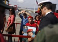 Supporters of Venezuela's late President Hugo Chavez line up to view his body in state at the Military Academy in Caracas March 7, 2013. REUTERS/Tomas Bravo