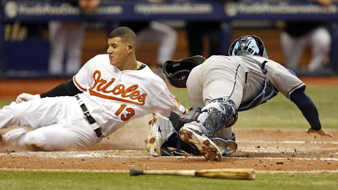 Baltimore Orioles' Manny Machado (13) slides in ahead of a tag by Tampa Bay Rays catcher Rene Rivera during the sixth inning of a baseball game Sunday, May 3, 2015, in St. Petersburg, Fla. The game was moved from Baltimore to St. Petersburg due to civil unrest. (AP Photo/Mike Carlson)