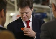 Britain's Deputy Prime Minister Nick Clegg removes a sticker supporting Liberal Democrats Eastleigh by-election candidate Mike Thornton, during a visit to the Aston Martin production facility in Gaydon, central England February 28, 2013. REUTERS/Darren Staples