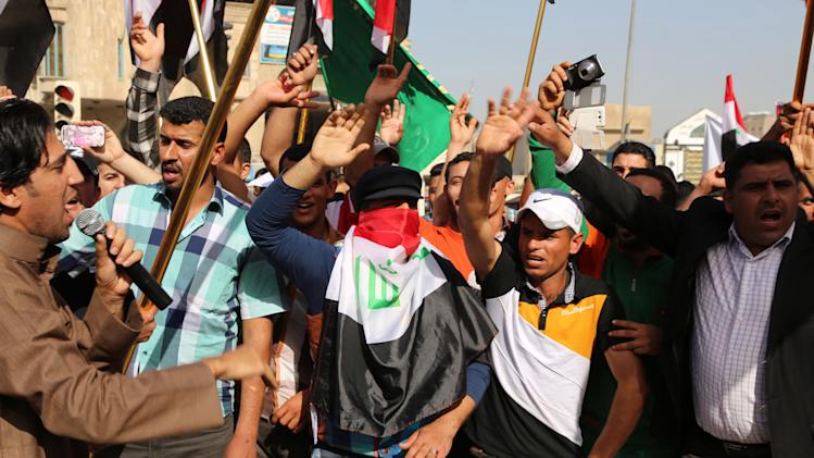 Protesters chant anti-Iraqi government slogans while waving national flags during a protest against the Iraqi parliament at Tahrir Square in Baghdad, Iraq, Saturday, March 8, 2014. (AP Photo/Karim Kadim)