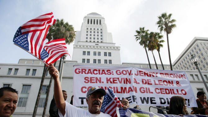 Ipolito Nurez celebrates outside City Hall after California Gov. Jerry Brown signed the bill AB 60, which allows immigrants in the country illegally to obtain driver licenses. Immigrant advocates have long lobbied for the change in the nation's most populous state so immigrants can drive without fearing being pulled over for a ticket, which could wind up getting them deported. (AP Photo/Nick Ut)