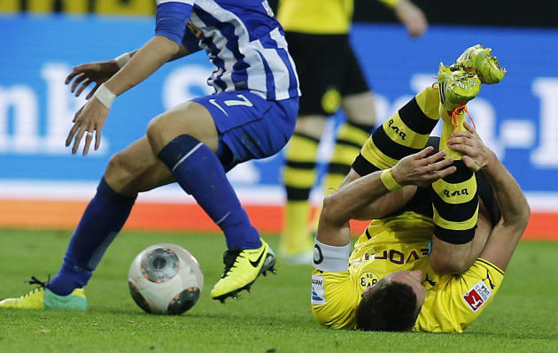 Dortmund's Sebastian Kehl lies on the pitch after challenging  for the ball with Berlin's Hajime Hosogai of Japan during the German first division Bundesliga soccer match between Borussia Dort