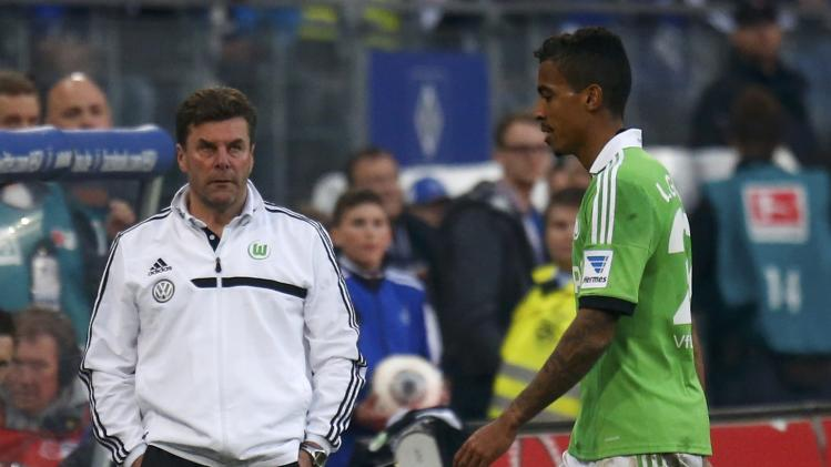 VfL Wolfsburg's coach Hecking looks at Gustavo leaving pitch after being sent off during their German first division Bundesliga soccer match against Hamburger SV in Hamburg