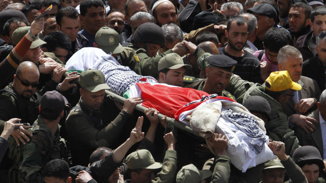 Palestinian security forces carry the body of Maysara Abu Hamdiyeh, center, during his funeral in the West Bank city of Hebron, Thursday, April 4, 2013. Demonstrations first erupted across the West Bank on Tuesday over the death of a Palestinian prisoner who died from cancer. The prisoner, 64-year-old Maysara Abu Hamdiyeh, was serving a life sentence for a 2002 foiled bombing of a busy Jerusalem cafe. After Abu Hamdiyeh died, the Palestinians blamed Israel for the death, saying he was not given proper medical care. Israel says the prisoner was treated by specialist doctors in hospital.(AP Photo/Nasser Shiyoukhi)