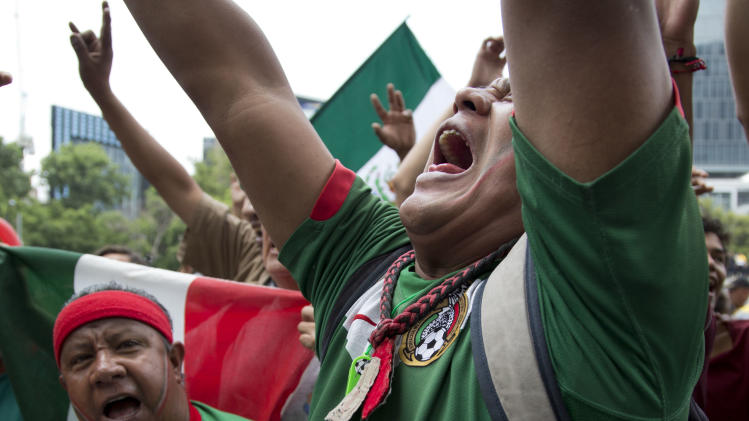 Mexico soccer fans react after their team was defeated on the World Cup round of 16 match against Netherlands at the independence monument in Mexico City, Sunday, June 29, 2014. The Netherlands staged a dramatic late comeback, scoring two goals in the dying minutes to beat Mexico 2-1 and advance to the World Cup quarterfinals. (AP Photo/Moises Castillo)