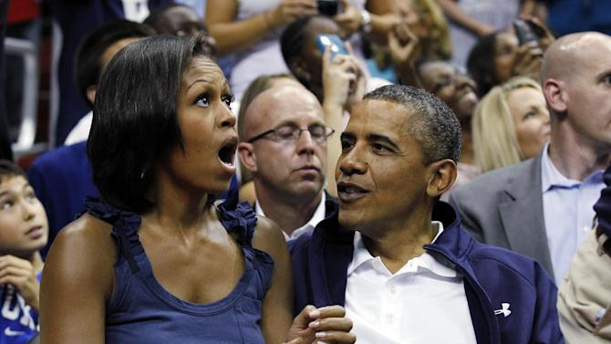 "President Barack Obama, left, and first lady Michelle Obama, look up at themselves on the large in-house video screen as they appear on ""Kiss Cam', while watching the first half of Team USA and Brazil in an Olympic men's exhibition basketball game, Monday, July 16, 2012, in Washington. Team USA won 80-69. (AP Photo/Alex Brandon)"