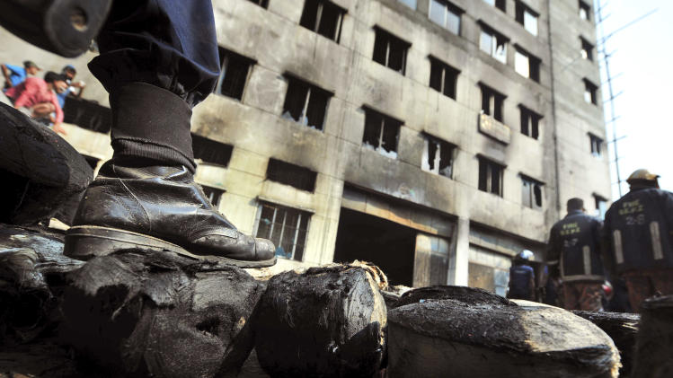 A Bangladeshi police officer stands guard outside the burnt garment factory outside Dhaka, Bangladesh, Sunday, Nov. 25, 2012. At least 112 people were killed in a late Saturday night fire that raced through the multi-story garment factory just outside of Bangladesh's capital, an official said Sunday. (AP Photo/ khurshed Rinku)