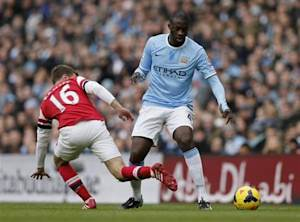 Manchester City's Toure is challenged by Arsenal's Ramsey during their English Premier League soccer match at the Etihad stadium in Manchester