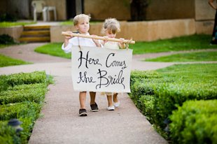 Pillow boy and flower girl carrying sign.