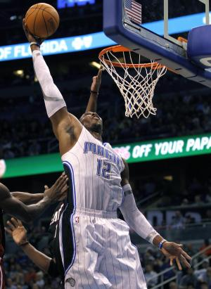 Orlando Magic center Dwight Howard (12) dunks the ball around Miami Heat forward Chris Bosh (1) during the first half of an NBA preseason basketball game, Wednesday, Dec. 21, 2011, in Orlando, Fla. (AP Photo/Reinhold Matay)
