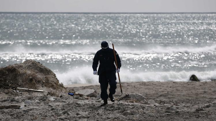 A police officer searches for missing people of the March 11, 2011 earthquake and tsunami along the coast side in Namie town, Fukushima prefectur
