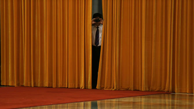 A Chinese man takes photos with his camera phone from behind curtains before a welcome ceremony for German Chancellor Angela Merkel at the Great Hall of the People in Beijing Thursday, Aug. 30, 2012. (AP Photo/Ng Han Guan)