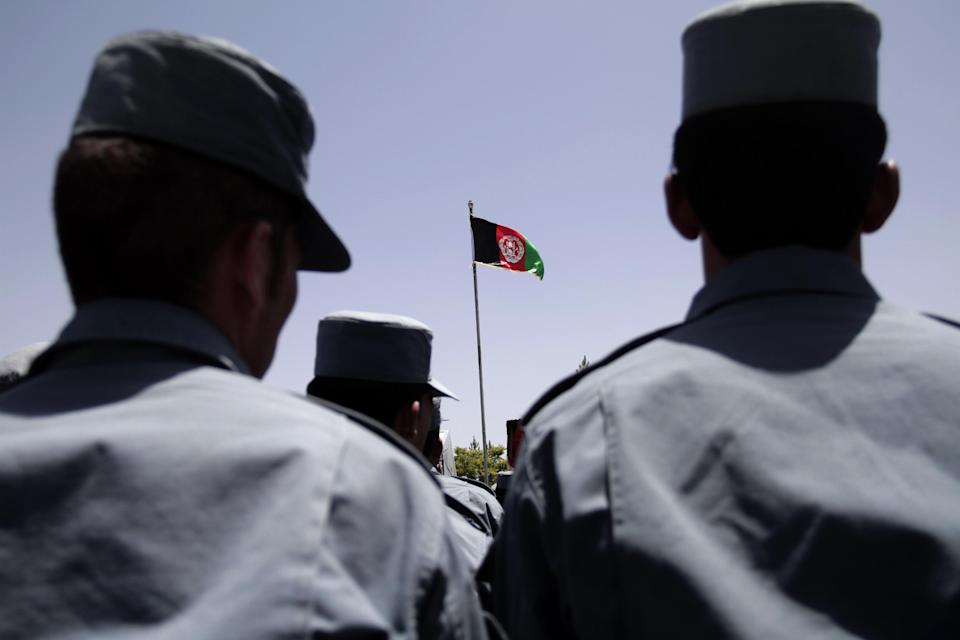 Afghan officials unfurl the national flag during the fifth phase of a transfer of authority ceremony of the police academy from NATO-led troops to Afghan security forces in Kabul, Afghanistan, Saturday, June 22, 2013. (AP Photo/Rahmat Gul)