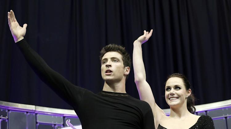Second-placed Tessa Virtue and Scott Moir, of Canada, wave as they after watching their scores during the free skate program in the ice dancing competition at the World Figure Skating Championships Saturday, March 16, 2013, in London, Ontario. (AP Photo/Darron Cummings)
