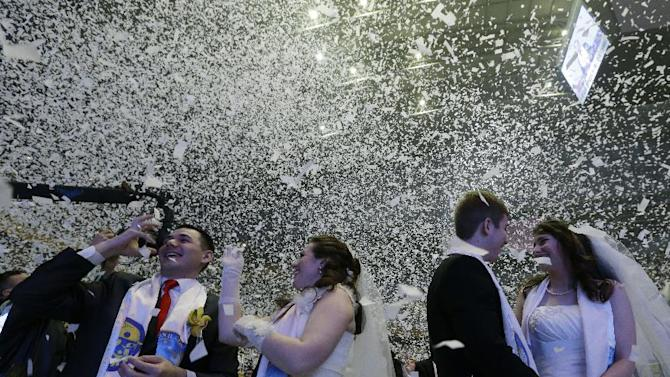 Couples from around the world celebrate after a mass wedding ceremony at the Cheong Shim Peace World Center in Gapyeong, South Korea, Tuesday, March 3, 2015. Some 3,800 South Korean and foreign couples exchanged or reaffirmed marriage vows in the Unification Church's mass wedding arranged by Hak Ja Han Moon, wife of the late Rev. Sun Myung Moon, the controversial founder of the Unification Church. (AP Photo/Ahn Young-joon)