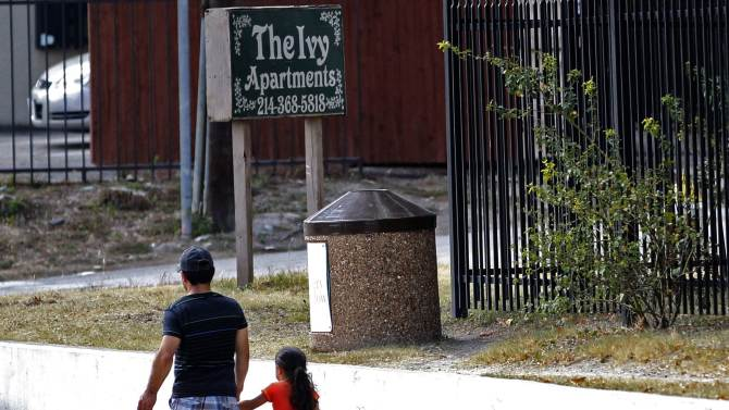 A man and young girl walk past The Ivy Apartments where a man diagnosed with the Ebola virus was staying in Dallas