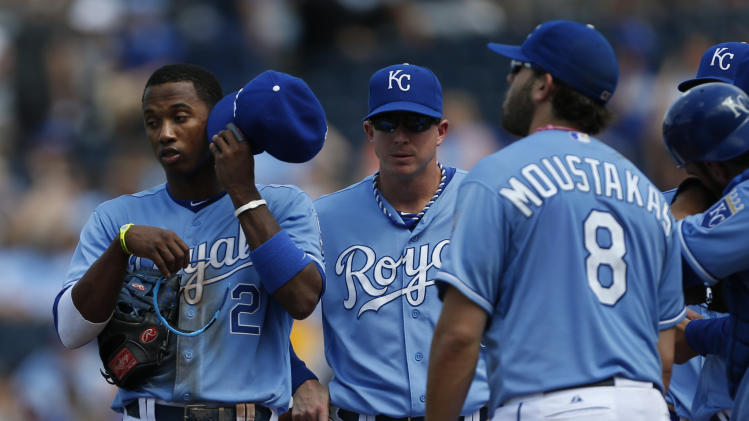 Kansas City Royals shortstop Alcides Escobar (2), second baseman Chris Getz and third baseman Mike Moustakas (8) wait during a pitching change in the eighth inning of the MLB American League baseball game against the Los Angeles Angels at Kauffman Stadium in Kansas City, Mo., Saturday, May 25, 2013. (AP Photo/Orlin Wagner)