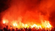 Galatasaray's supporters light flares during the UEFA Champions League quarter-final first leg football match Real Madrid vs Galatasaray on April 3, 2013 at Santiago Bernabeu stadium in Madrid. Real won 3-0