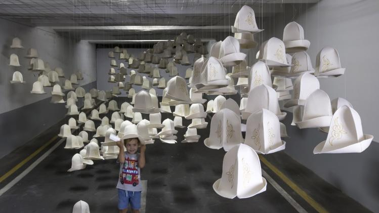 A boy plays at an installation called Kyrgyz Pass, made of national felt hats, by artist Syrlybek Bekbotayev during the contemporary art Artbat festival in Almaty