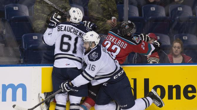 Rimouski Oceanics' Francois Beauchemin, left, and Justin Vachon, center, check Kelowna Rockets' Justin Kirkland during second period of a game in the Memorial Cup hockey tournament Monday, May 25, 2015, in Quebec City, Quebec. (Jacques Boissinot/The Canadian Press via AP) MANDATORY CREDIT