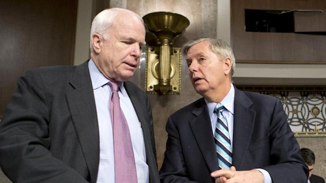 FILE - In this Feb. 14, 2013 file photo, Sen. John McCain, R-Ariz., left, and Sen. Lindsey Graham, R-S.C. confer on Capitol Hill in Washington. McCain, Sen. Lindsey Graham, R-S.C., Sen. and Jeff Flake, R-Ariz. met with key House conservatives this week to promote legislation to overhaul the nation's immigration laws and provide a pathway to citizenship for an estimated 11 million illegal immigrants, McCain's communications director said Friday. (AP Photo/J. Scott Applewhite, File)