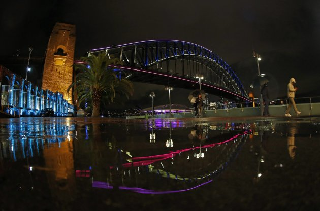 Pedestrians walk past the Sydney Harbour Bridge lit up in colours as part of Vivid Festival in Sydney