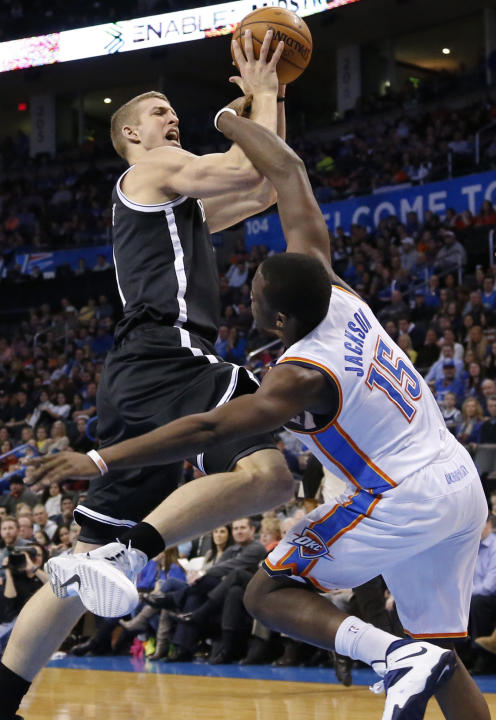 Brooklyn Nets forward Mason Plumlee is fouled by Oklahoma City Thunder guard Reggie Jackson (15) in the first quarter of an NBA basketball game in Oklahoma City, Thursday, Jan. 2, 2014. (AP Photo/Sue