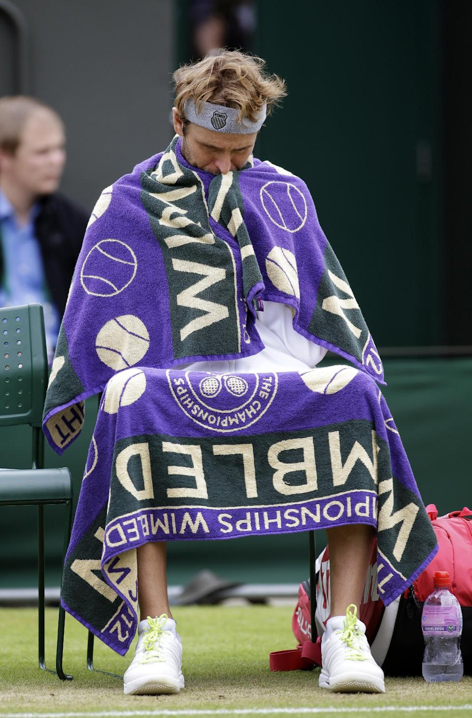 Mardy Fish of the United States waits as Jo-Wilfried Tsonga of France is checked by a trainer during a fourth round singles match at the All England Lawn Tennis Championships at Wimbledon, England, Tuesday, July 3, 2012. (AP Photo/Sang Tan)