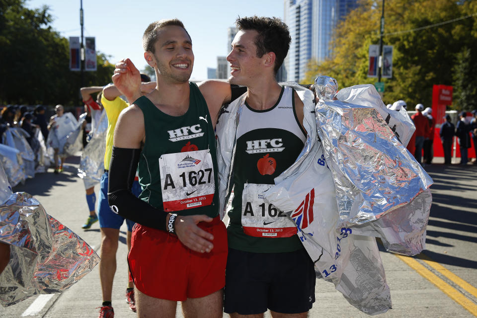 Andrew Holmes, left, of Newton, Mass., and Peter Ryan, right, of Holden, Mass., celebrate after finishing the Chicago Marathon on Sunday, Oct. 13, 2013, in Chicago. (AP Photo/Andrew A. Nelles)