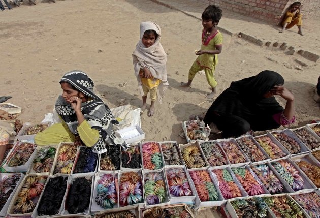 Children stand near their mothers selling bangles at a stall outside the Sufi shrine of Baba Gharib Sha