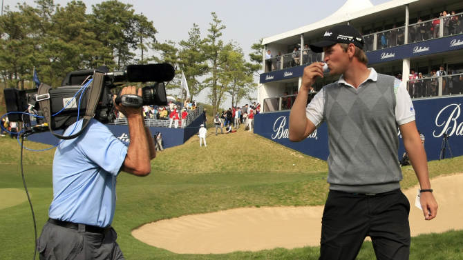 Bernd Wiesberger of Austria kisses a ball after finishing his play in the third round of the Ballantine's Championship golf tournament at the Black Stone Golf Club in Icheon, South Korea, Saturday, April 28, 2012. Wiesberger shot 202 to lead the championship. (AP Photo/Lee Jin-man)