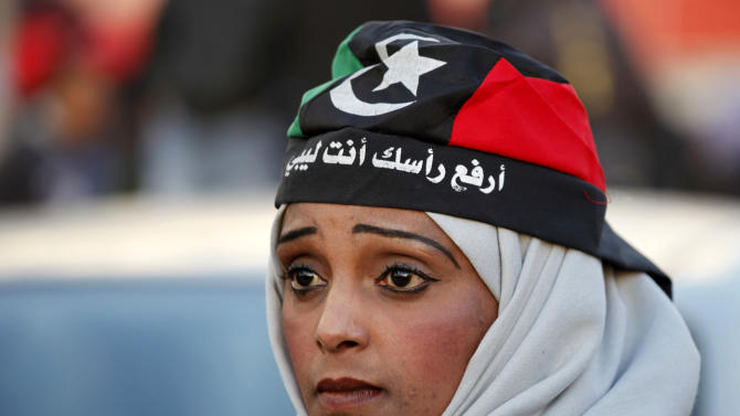 "FILE - In this Friday, Feb. 15, 2013 file photo, a Libyan woman wearing a depiction of the national flag bearing the words, ""hold your head high, you are Libyan,"" attends commemorations to mark the second anniversary of the revolution that ousted Moammar Gadhafi in Benghazi, Libya. Women played a major role in the 8-month civil war against dictator Moammar Gadhafi, massing for protests against his regime, selling jewelry to fund rebels, helping treat the wounded, smuggling weapons across enemy lines to rebels. But since Gadhafi's fall more than 18 months ago, women have been rewarded by seeing rights they enjoyed under his rule hemmed in and restricted. (AP Photo/Mohammad Hannon, File)"
