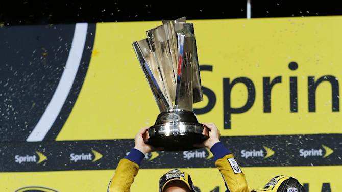 Brad Keselowski holds up his trophy after winning the NASCAR Sprint Cup Series championship following an auto race at Homestead-Miami Speedway, Sunday, Nov. 18, 2012, in Homestead, Fla. Keselowski clinched the title after fellow contender Jimmie Johnson pulled out of the season finale because of a parts failure. Jeff Gordon won the race. (AP Photo/Terry Renna)