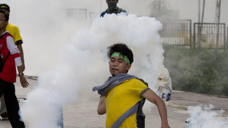 A protester throws a tear gas canister back at police in Kuala Lumpur, Malaysia, Saturday, April 28, 2012. Malaysian police fired tear gas and chemical-laced water Saturday at thousands of demonstrators demanding an overhaul in electoral policies that they call biased ahead of national polls expected soon.At least 25,000 demonstrators had swamped Malaysia's largest city in one of the Southeast Asian nation's biggest street rallies in the past decade. (AP Photo/Mark Baker)