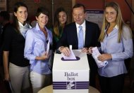 Tony Abbott (2nd R), who leads the conservative opposition, casts his vote as his wife Margaret and daughters Louise, Frances and Bridget (L-R) look on at the Freshwater Beach Surf Lifesaving Club in Sydney, on election day September 7, 2013. REUTERS/David Gray