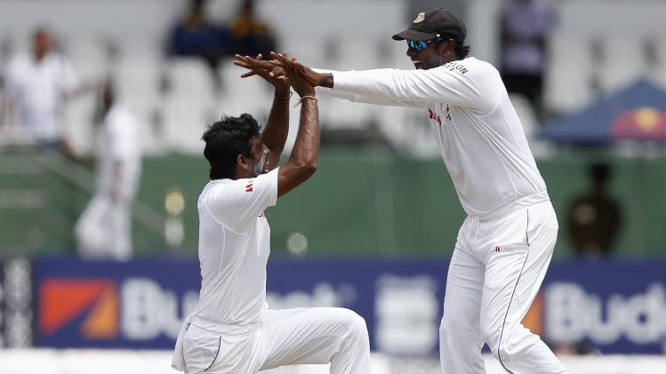 Sri Lanka's Perera celebrates with captain Mathews after taking the wicket of South Africa's de Villiers during the third day of their second test cricket match in Colombo