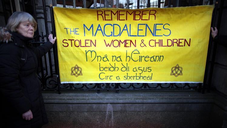 A woman hold a poster as relatives of victims of the Magdalene Laundries hold a candle lit vigil in solidarity with Justice for Magdalene Survivors and their families outside Leinster House, Dublin,Ireland, Tuesday, Feb. 19, 2013. The women expect to witness an apology by the Irish Prime Minister Enda  Kenny on behalf of the people of Ireland for ignoring them and their treatment at the 10 laundries in the Republic between 1922 and 1996. The women will also hear details of how the State intends to assist them financially and in other ways as restitution. (AP Photo/Peter Morrison)