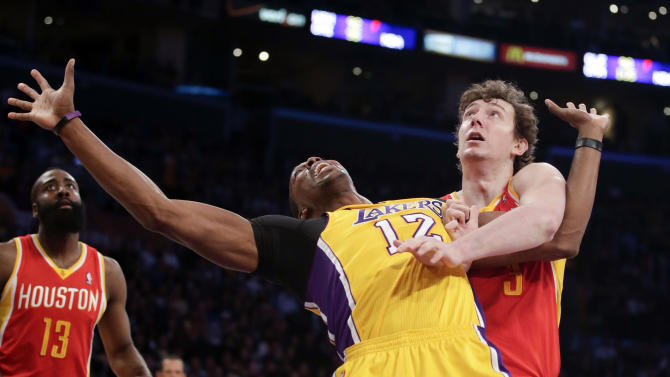 Los Angeles Lakers' Dwight Howard, center, is fouled by Houston Rockets' Omer Asik, of Turkey, during the first half of an NBA basketball game in Los Angeles, Wednesday, April 17, 2013. (AP Photo/Jae C. Hong)