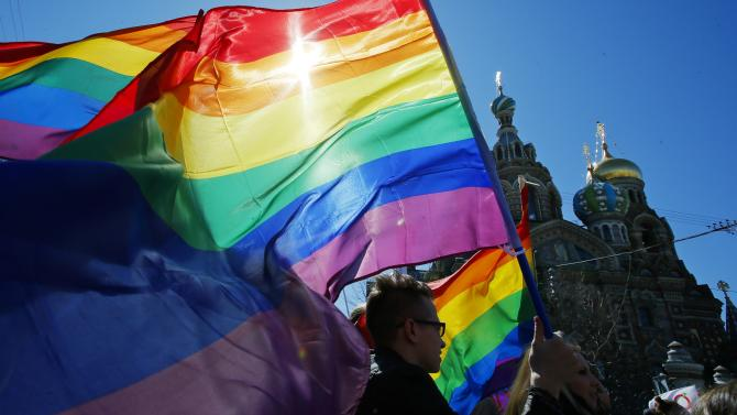 """FILE - In this Wednesday, May 1, 2013, file photo, gay rights activists carry rainbow flags as they march during a May Day rally in St. Petersburg, Russia. With the Winter Olympic Games in Sochi set to start in February, Russia has trotted out well-groomed representatives to tell the West that a law passed this summer banning homosexual """"propaganda"""" does not discriminate against gays. Meanwhile, the Russian government has doubled down on the anti-LGBT rhetoric at home, unifying its fraying electoral base with a popular refrain of traditional values. (AP Photo/Dmitry Lovetsky, File)"""
