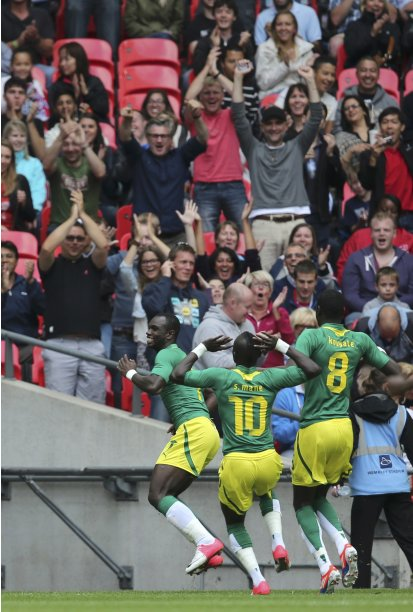 Senegal's Moussa Konate celebrates his goal with Sadio Mane and Cheikhou Kouyate during their men's preliminary first round Group A soccer match against Uruguay at the London 2012 Olympic Games in the Wembley Stadium in London