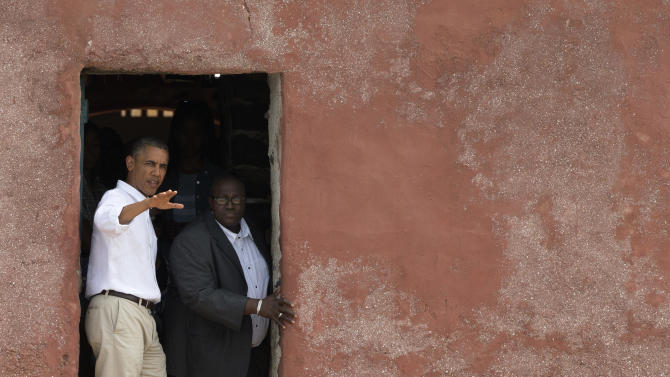 U.S. President Barack Obama, left, talks with Slave House curator Eloi Coly, as they look out to sea through the 'Door of No Return,' on Goree Island, in Dakar, Senegal, Thursday, June 27, 2013. Obama is calling his visit to a Senegalese island from which Africans were said to have been shipped across the Atlantic Ocean into slavery, a 'very powerful moment.' President Obama was in Dakar Thursday as part of a weeklong trip to Africa, a three-country visit aimed at overcoming disappointment on the continent over the first black U.S. president's lack of personal engagement during his first term.(AP Photo/Rebecca Blackwell)