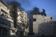 In this Wednesday, Dec. 5, 2012 photo, smoke rises from residential buildings due heavy fighting between Free Syrian Army fighters and government forces in Aleppo, Syria. (AP Photo/Narciso Contreras)