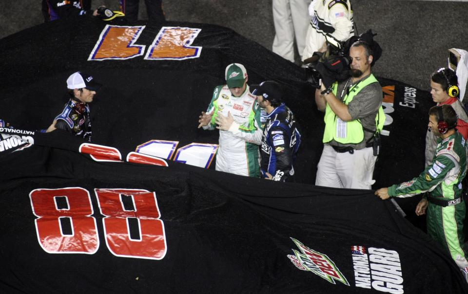 Dale Earnhardt Jr., center left, talks with Jimmie Johnson, center right, during a rain delay at the NASCAR Sprint Cup Series auto race at Richmond International Raceway in Richmond, Va., Saturday, Sept. 8, 2012. (AP Photo/Jason Hirschfeld)