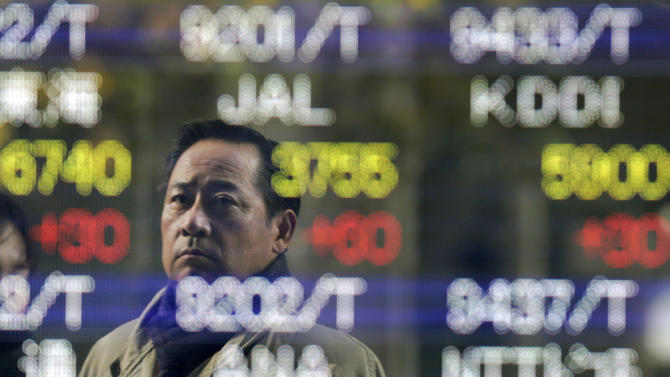 A man checks the electronic stock board of a securities firm in Tokyo, Tuesday, Dec. 18, 2012. Asian stock markets were mostly higher Tuesday, boosted by signs China's recovery is gaining traction and hopes for a new stimulus in Japan. (AP Photo/Itsuo Inouye)