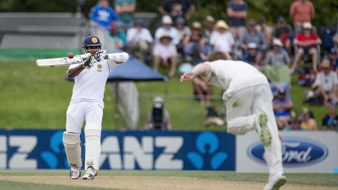 Sri Lanka's Dilruwan Perera (L) plays a shot against New Zealand bowler Trent Boult during day two of the first International Test cricket match between New Zealand and Sri Lanka at Hagley Park Oval in Christchurch on December 27, 2014