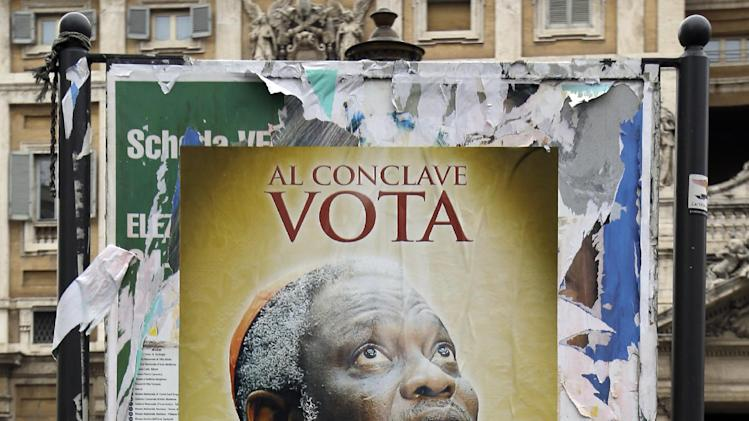 "FILE - This March 1, 2013 file photo shows a poster with a picture of Nigerian Cardinal Peter Kodwo Appiah Turkson with writing reading: ""For the next conclave vote for Turkson"", in front of the St. Mary Major Basilica in Rome. These are crazy days in Rome - where limbo reigns in parliament and papacy. Italy is usually a pretty anarchic place, with people bucking rules on everything from crossing the street to paying taxes. But the anarchy's going a bit far: Who's running the country? Who's running the church? Nobody really knows. (AP Photo/Gregorio Borgia, files)"