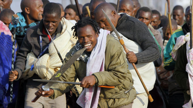 Striking miners sing, chant, march and dance with crudely made weapons and machetes at the Lonmin mine near Rustenburg, South Africa, Wednesday Aug. 15, 2012. Ongoing violence that started last Friday has seen 10 people killed, with no end to the strike in sight. (AP Photo/Denis Farrell)