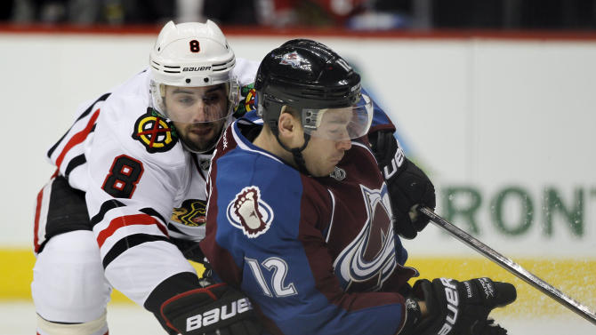 Chicago Blackhawks defenseman Nick Leddy, left, is called for a holding penalty as he tries tostop Colorado Avalanche right wing Chuck Kobasew in the first period of an NHL hockey game in Denver, Friday, March 8, 2013. (AP Photo/David Zalubowski)