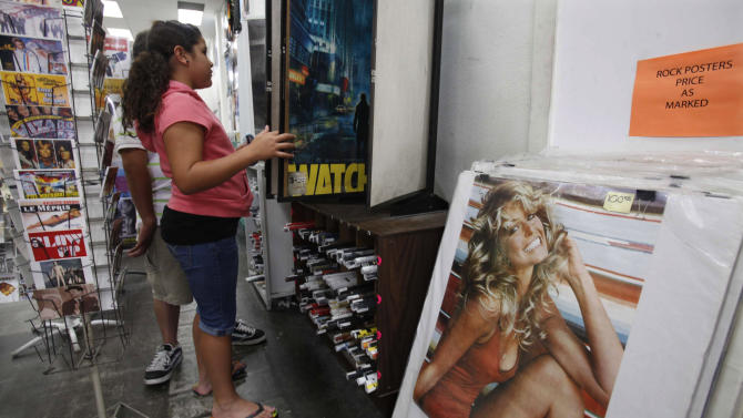 FILE - In this June 25, 2009 file photo, a poster of Farrah Fawcett is shown for sale in a tourist shop as Andrea Diaz looks at posters in the Hollywood section of Los Angeles. The red swimsuit that helped make Fawcett an icon is going to the Smithsonian. (AP Photo/Nick Ut, File)