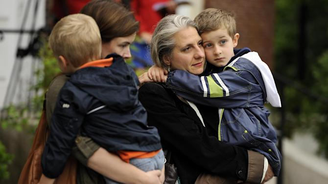 Lauren Brenneman, left, holds her son Isaac Brenneman as friend Valerie Guerin holds her son Stephen Guerin during a ceremony on the six month anniversary honoring the 20 children and six adults gunned down at Sandy Hook Elementary School on Dec. 14,2012, at Edmond Town Hall in Newtown, Conn., Friday, June 14, 2013. Newtown held a moment of silence Friday for the victims of the massacre at Sandy Hook Elementary School at a remembrance event that doubled as a call to action on gun control, with the reading of names of thousands of victims of gun violence. (AP Photo/Jessica Hill)